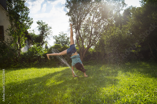 Girl having fun with lawn sprinkler in the garden