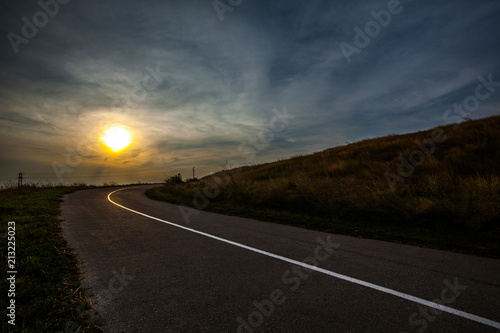 Foto op Canvas Olijf Field of golden grass. Empty asphalt road and dark blue sky during Sunset