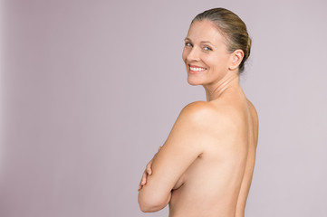 Senior woman standing naked