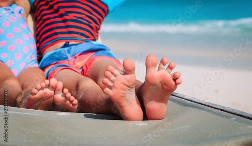 Fotografía  little boy and girl relax on beach, focus on feet
