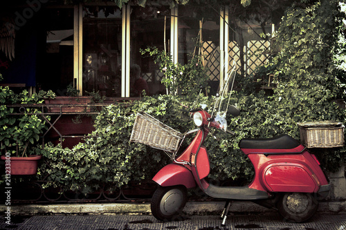 Fotobehang Scooter red vintage scooter in italy, retro motorcycle with foliage background