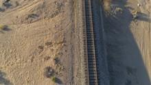 4K Aerial Pan Up Of Desert Train Tracks At Sunrise