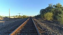 4K Aerial Descent Of Desert Train Tracks At Sunrise