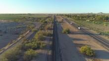 4K Aerial Dolly Shot Of Desert Train Tracks At Sunrise Near Highway