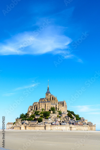 General view of the Mont Saint-Michel tidal island, located in France on the limit between Normandy and Brittany, with the exposed sand of the bay at low tide in the foreground under a blue sky Poster