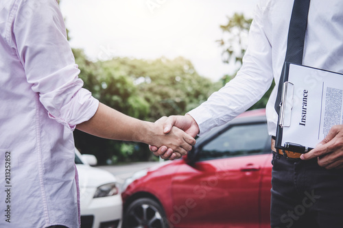 Insurance Agent and customer shaking hands after claim contact, Traffic Accident and insurance concept