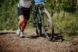 legs woman cyclist climbing uphill on trail mountain bike race