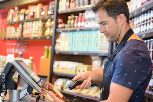 Shop clerk scanning bottle of alcohol Fototapete