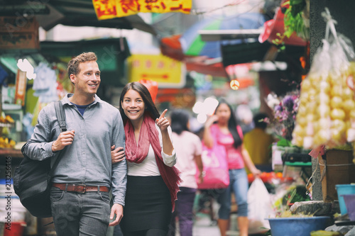 fototapeta na ścianę Interracial couple tourists walking shopping in chinese market in Hong Kong, China. Young people traveling in Asia looking at local street food. Asian woman, Caucasian man.