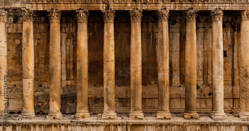 Frontal view of a colonnade - Row of columns of an ancient Roman temple ruin (Ba Canvas Print