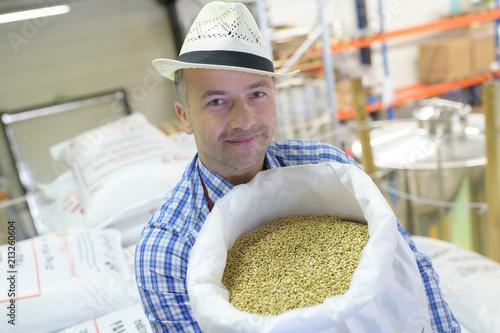 worker holding bag full of coffee beans Fototapeta
