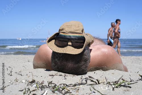 man sunbathes on the beach with a cap on the head Canvas-taulu