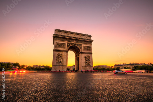 Arch of triumph at twilight. Arc de Triomphe at end of Champs Elysees in Place Charles de Gaulle with cars and trails of lights. Popular landmark and tourist attraction in Paris capital of France.