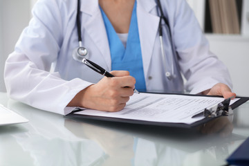 Doctor woman filling up medical form while sitting at the table, close-up of hands