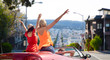 leisure, road trip, travel and people concept - happy friends driving in convertible car and waving hands over san francisco city background