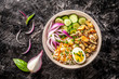 Hawaiian Pake salad with mussels, boiled egg, red onion, cucumber and rice, with black sesame. in a gray plate. On a black biton background. copy space, top view