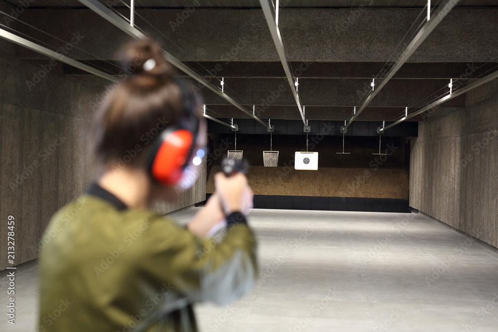 Fototapeta Na strzelnicy. Kobieta celuje do papierowej tarczy