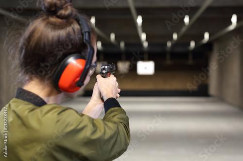 Fototapeta Strzelectwo. Kobieta celuje do papierowej tarczy obraz