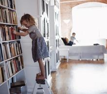 Girl Standing By Bookshelves On Ladder At Home