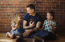 Happy Father With Children Eating Donuts While Sitting On Floor At Home