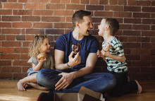 Father With Children Eating Donuts While Sitting On Floor At Home
