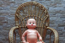 Doll In A Wooden Chair