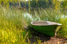 A Boat Moored On Tall Grass By...