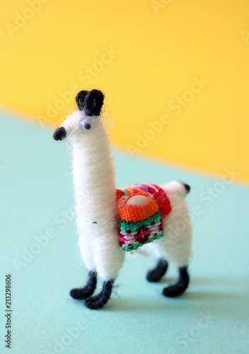 Fotobehang Lama Colorful, traditional, little Llama doll, handmade from Bolivia, standing on a geometrical yellow and turquoise background