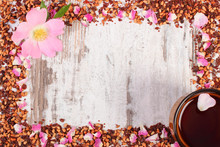 Frame Of Dried Wild Rose Petals And Tea Grains, Cup Of Tea, Copy Space For Text On Rustic Board