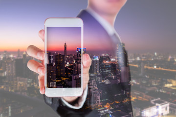 Double exposure of businessman hold and show smartphone display and cityscape in the night as business, technology, communication and advertising concept.