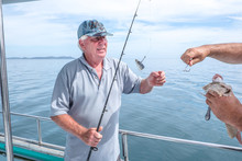 Fisherman Helping Caucasian To...
