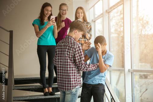 Photo  Teenager bullying African American boy indoors