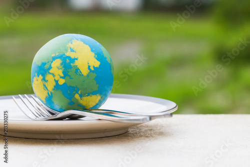Globe model placed on plate with fork spoon for serve menu in famous hotels. International cuisine is practiced around the world often associated with specific region country. World food inter concept