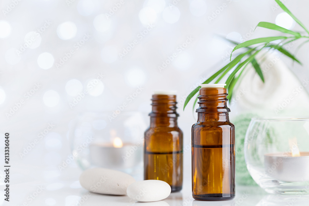 Fototapety, obrazy: Bottle with essential oil, towel and candles on white table. Spa, aromatherapy, wellness, beauty background.