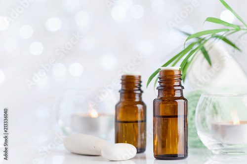 Bottle with essential oil, towel and candles on white table. Spa, aromatherapy, wellness, beauty background.