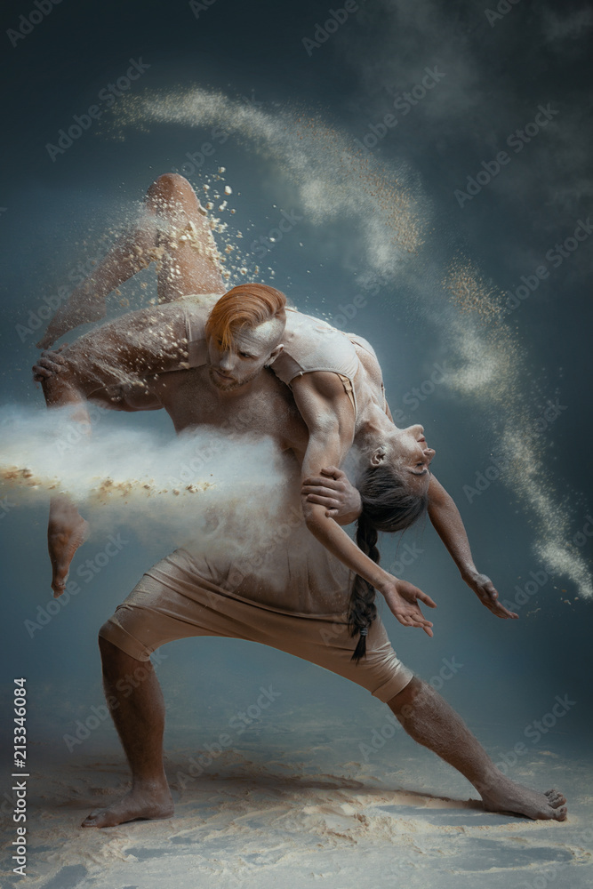 Fototapeta Dancing in flour concept. Guy male man and girl woman female dancers in dust / fog. Couple in love dancing and making dance element in flour cloud on isolated grey background