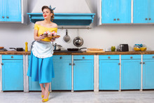 Retro Pin Up Girl Woman Female Housewife Wearing Colorful Top, Skirt And White Apron And Yellow High Heels Holding Tray With Sweet Cupcakes Standing In The Kitchen With Blue Cabinets And Utensils.