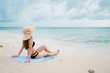 woman sitting on the seaside wear a bikini wearing a sea hat, the environment bright and clear.