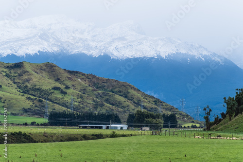 Tuinposter Landschappen Beautiful landscape of a green meadows and snow mountain in a cloudy day. Foggy over the mountains.