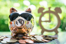 Cute Piggy Bank With Gold Coin And Wooden Clock With Green Bokeh Background.Buy Time Concept.