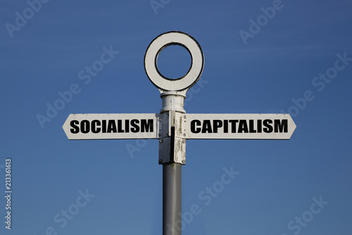 Fotografie, Tablou  Old road sign with socialism and capitalism pointing in opposite directions agai