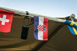 Small croatian flag fluttering on the wind, between two more flags. Croatia is one of the World Cup finalist.