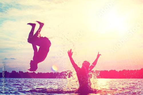 Foto  Glückliche junge Menschen laufen und springen am See beim Sonnenuntergang
