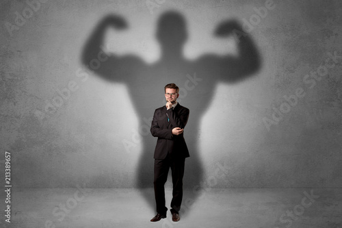 Spoed Foto op Canvas Wanddecoratie met eigen foto Lovely serious businessman standing with a muscular powerful shadow behind his back