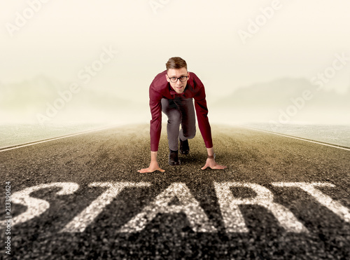 Photo  Young determined businessman kneeling at a start line