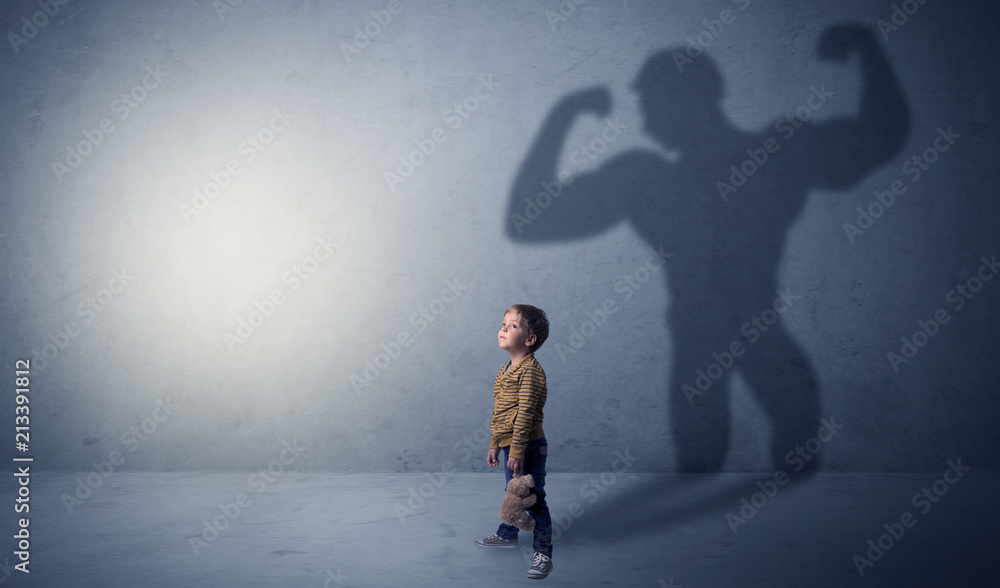Fototapety, obrazy: Little waggish boy in an empty room with musclemen shadow behind