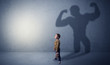 canvas print picture - Little waggish boy in an empty room with musclemen shadow behind
