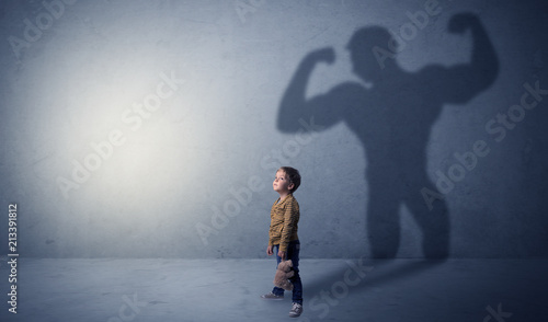 Photo  Little waggish boy in an empty room with musclemen shadow behind