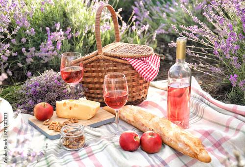 Obraz premium Zestaw na piknik na kocu w lawendowym polu