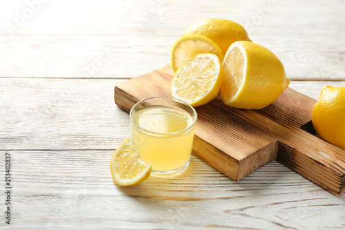 Glass with fresh lemon juice and fruits on table